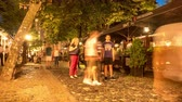 cena urbana : BELGRADE, SERBIA - CIRCA JUNE 2018: Time-lapse view on people as they pass by traditional restaurants and bars in the downtown of the city at night circa June 2018 in Belgrade, Serbia.