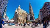 vídeň : VIENNA, AUSTRIA - CIRCA APRIL 2018: Time-lapse view on pedestrians as they pass by on the square front of the gothic building of the St. Stephens Cathedral on a sunny day circa April 2018 in Vienna, Austria.