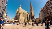viyana : VIENNA, AUSTRIA - CIRCA APRIL 2018: Time-lapse view on pedestrians as they pass by on the square front of the gothic building of the St. Stephens Cathedral on a sunny day circa April 2018 in Vienna, Austria.