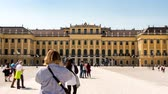 monarşi : VIENNA, AUSTRIA - CIRCA APRIL 2018: Panorama time-lapse view on the baroque architecture of the Schoenbrunn Palace as tourist pass by at the lake and on the walkway of the castle park circa April 2018 in Vienna, Austria.