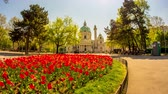 monarşi : VIENNA, AUSTRIA - CIRCA APRIL 2018: Timelapse view on the iconic Charles square as people pass by on the walkways in the park front of the historic building of Charles Church on a sunny day circa April 2018 in Vienna, Austria