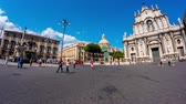 sicílie : CATANIA, ITALY - CIRCA JUNE 2018:  Time-lapse view on the Main Square with the Baroque style Catania Cathedral in the background as pedestrians pass by on a sunny day circa June 2018 in Catania, Italy.
