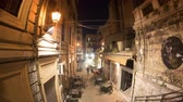 sicílie : PALERMO, ITALY - CIRCA JUNE 2018: Time-lapse view on people as they pass by on the historic street with a restaurant of the city centre at night circa June 2018 in Palermo, Italy. Dostupné videozáznamy