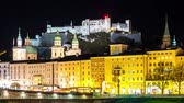 austrian : SALZBURG, AUSTRIA - CIRCA APRIL 2018: Time-lapse view on the historic architecture at the riverbank in the downtown as city lights are reflected on the through flows river Salzach at night circa April 2018 in Salzburg, Austria.