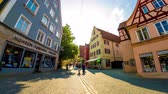 булыжник : NOERDLINGEN, GERMANY - CIRCA SEPTEMBER 2018: Time-lapse view on daily life as pedestrians pass by on the streets in the historic centre of the city on a sunny day circa September 2018 in Noerdlingen, Germany