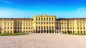 imperial : VIENNA, AUSTRIA - CIRCA APRIL 2018: Time-lapse view on the baroque architecture of the Schoenbrunn Palace as tourist pass by on the walkway of the castle park circa April 2018 in Vienna, Austria.