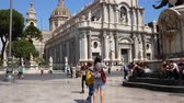 godo : CATANIA, ITALY - CIRCA JUNE 2018:  View on historic architecture as pedestrians and traffic pass by on the cobblestones street of the city centre on a sunny day circa June 2018 in Catania, Italy.