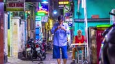 streetfood : HO CHI MINH CITY, VIETNAM - CIRCA FEBRUARY 2018: Time-lapse view of daily life as people pass by on a side street in the downtown at night circa February 2018 in Ho Chi Minh City, Vietnam.