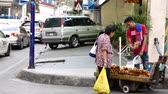 banan : METRO MANILA, PHILIPPINES - CIRCA MARCH 2018: View on a street vendor as people pass by at his banana stall circa March 2018 in Metro Manila, Philippines. Wideo