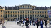 viyana : VIENNA, AUSTRIA - CIRCA APRIL 2018: the Baroque architecture of the Schoenbrunn Palace as tourist pass by on the walkway of the castle park circa April 2018 in Vienna, Austria.
