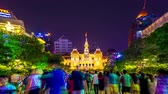 인도 차이나 : HO CHI MINH CITY, VIETNAM - CIRCA FEBRUARY 2018: Time-lapse view on people as they pass by the illuminated building of City Hall at night circa February 2018 in Ho Chi Minh City, Vietnam.