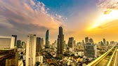 apartment buildings : BANGKOK, THAILAND - CIRCA MARCH 2018: Time-lapse view on the skyline of the city from a rooftop as traffic passes by on the streets during dusk circa March, 2018 in Bangkok, Thailand.