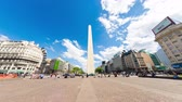 arjantin : BUENOS AIRES, ARGENTINA - CIRCA FEBRUARY 2019: Time-lapse view on People pass by in front of the famous Obelisk landmark in the center of the city circa February 2019 in Buenos Aires, Argentina. Stok Video
