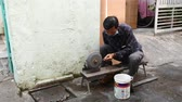 нож : HO CHI MINH CITY, VIETNAM - CIRCA FEBRUARY 2018: A knife sharpener man works with whetstone on the street circa February 2018 in Ho Chi Minh City, Vietnam.