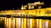 Австрия : SALZBURG, AUSTRIA - CIRCA APRIL 2018: Time-lapse view on the historic architecture at the riverbank in the downtown as city lights are reflected on the  river Salzach at night circa April 2018 in Salzburg, Austria.