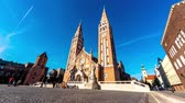fresk : SZEGED, HUNGARY - CIRCA APRIL 2019: Time-lapse view on the famous Cathedral as visitors pass by at the church circa April 2019 in Szeged, Hungary. Stok Video