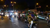 夜遊び : HO CHI MINH CITY, VIETNAM - CIRCA FEBRUARY 2018: View on traffic as cars and motorbikes pass by on a broad street at night circa February 2018 in Ho Chi Minh City, Vietnam. 動画素材