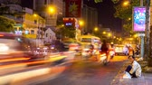 éjszakai : HO CHI MINH CITY, VIETNAM - CIRCA FEBRUARY 2018: Time-lapse view on a busy road as motorbikes and pedestrians pass by at night circa February 2018 in Ho Chi Minh City, Vietnam.