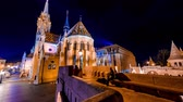 hungria : BUDAPEST, HUNGARY - CIRCA APRIL 2019: Time-lapse view on visitors in the illuminated Fishermans Bastion in the evening circa April 2019 in Budapest, Hungary.