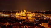 bastião : BUDAPEST, HUNGARY - CIRCA APRIL 2019: Time-lapse view on the illuminated building of the Hungarian Parliament from the tower of the Fishermans bastion circa April 2019 in Budapest, Hungary.
