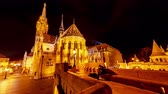 bastião : BUDAPEST, HUNGARY - CIRCA APRIL 2019: Time-lapse view on visitors in the illuminated Fishermans Bastion in the evening circa April 2019 in Budapest, Hungary.