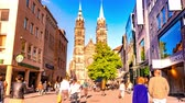 NUREMBERG, GERMANY - CIRCA MAY 2019: Time-lapse view on daily life as people pass by in the old town with the famous church St. Lawrence in the background circa May 2019 in Nuremberg, Germany.