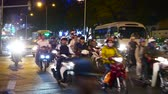 nachtleven : HO CHI MINH CITY, VIETNAM - CIRCA FEBRUARY 2018: View on traffic as cars and motorbikes pass by on a broad street at night circa February 2018 in Ho Chi Minh City, Vietnam. Stockvideo
