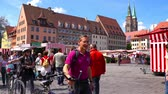 NUREMBERG, GERMANY - CIRCA MAY 2019: View on people as they visit the local market on a central square circa May 2019 in Nuremberg, Germany. Стоковые видеозаписи