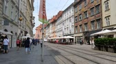GRAZ, AUSTRIA - CIRCA AUGUST 2019: View on a busy street in the centre of the city as traffic and pedestrians pass by circa August 2019 in Graz, Austria. Stok Video
