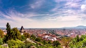 GRAZ, AUSTRIA - CIRCA AUGUST 2019: Time-lapse view over the famous Uhrturm on the Schlossberg and the city circa August 2019 in Graz, Austria.