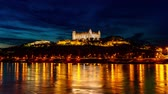 BRATISLAVA, SLOVAKIA - CIRCA AUGUST 2019: Time-lapse view on the nightfall over the Castle of the city and the river Danube circa August 2019 in Bratislava, Slovakia.