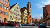 DINKELSBUEHL, GERMANY - CIRCA AUGUST 2019: View on the historic old town of the city as traffic and pedestrians pass by circa August 2019 in Dinkelsbuehl, Germany. Stok Video