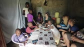 chata : KISUMU,KENYA - MAY 23, 2018: Big group of people sitting in poor house of African family. Caucasian men and women talk Dostupné videozáznamy