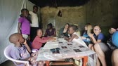 pobre : KISUMU,KENYA - MAY 23, 2018: Group of Caucasian people sitting in the house of poor African family and talking to them.