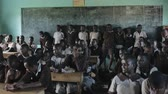 lição : KISUMU,KENYA - MAY 21, 2018: Crowd of happy African children in school. Boys and girls, teenagers smile and laugh.