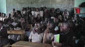 племя : KISUMU,KENYA - MAY 21, 2018: View of the large classroom full of African children. Boys and girls smile and stand up.