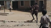 needy : KISUMU,KENYA - MAY 15, 2018: Group of african children in uniform playing football outside the school together, enjoying summer day.