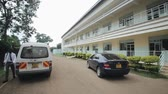 imunização : KENYA, KISUMU - MAY 20, 2017: Beautiful new building of African hospital. Doctors and cars is passing near the hosp.