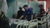 imunização : KENYA, KISUMU - MAY 20, 2017: Caucasian men in African hospital talking with people. Volunteers helping to local people.