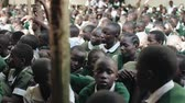 KENYA, KISUMU - MAY 20, 2017: Close-up view of African boys and girls sitting in a big crowd of pupils outside school. Stock Footage