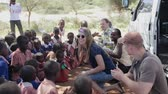 KENYA, KISUMU - MAY 20, 2017: Happy caucasian woman and man show movement, dance with African children. Stock Footage