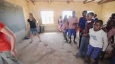 KENYA, KISUMU - MAY 20, 2017: Happy Caucasian women dancing with African children in small local school.