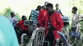 KENYA, KISUMU - MAY 20, 2017: Musical group is playing outside. African people, men in red jackets is preparing to show. Stock Footage