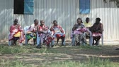 KENYA, KISUMU - MAY 20, 2017: Women with children from a local African tribe sitting on chairs.