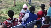 KENYA, KISUMU - MAY 20, 2017: Women with children from a local African tribe, maasai sitting on chairs.