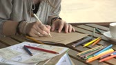 It is close-up image of female artist drawing picture with pencil Vídeos
