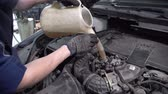 lubrication : Specialist the service station to fill in oil using a watering can. Stock Footage