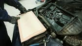 replacement : In service station mechanic installs a new air filter inside the box.