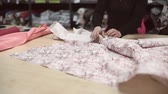 портниха : Woman separate from roll right amount of tissue with Japanese pattern. On wooden table white cloth with brown branches and pink flowers lay. y or atelier. Стоковые видеозаписи