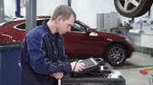 düzeltmek : Mechanic standing at the bar and tap the screen to diagnose. He stands on the background of a red expensive car and looks carefully at the device.